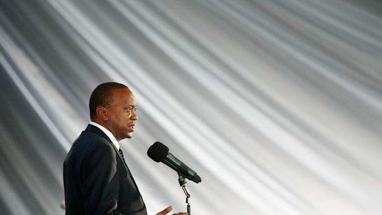 Kenyan President Uhuru Kenyatta pays tribute to his nephew Mbugua Mwangi and his fiancee Rosemary Wahito at their funeral service in Nairobi, Kenya, Friday Sept. 27, 2013. Mwangi and Wahito died in the the Westgate Mall attack. (AP Photo/Jerome Delay)