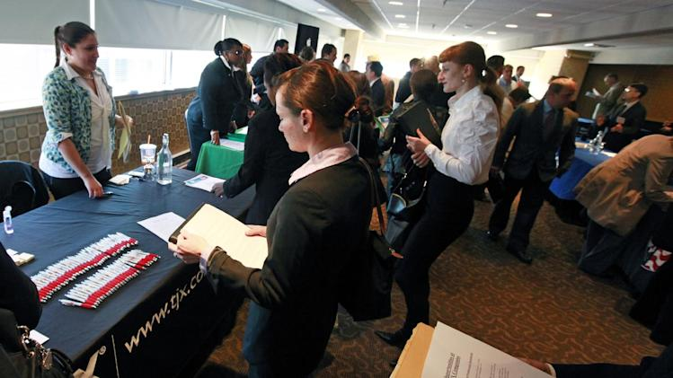 Job seekers crowd around tables to get information and drop off resumes during a job fair in Boston Monday, Oct. 17, 2011. Fewer people likely applied for unemployment benefits last week, suggesting the job market may be improving slightly. (AP Photo/Elise Amendola)