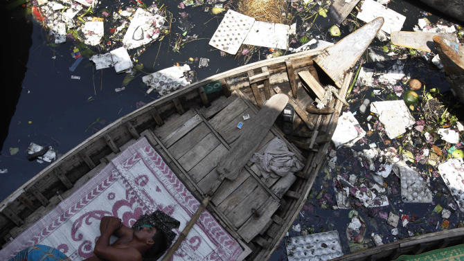 A boatman sleeps in his boat anchored in the polluted waters of the River Buriganga in Dhaka, Bangladesh, Sunday, April 22, 2012. April 22 is observed as Earth Day every year as a tool to raise ecological awareness. (AP Photo/Pavel Rahman)