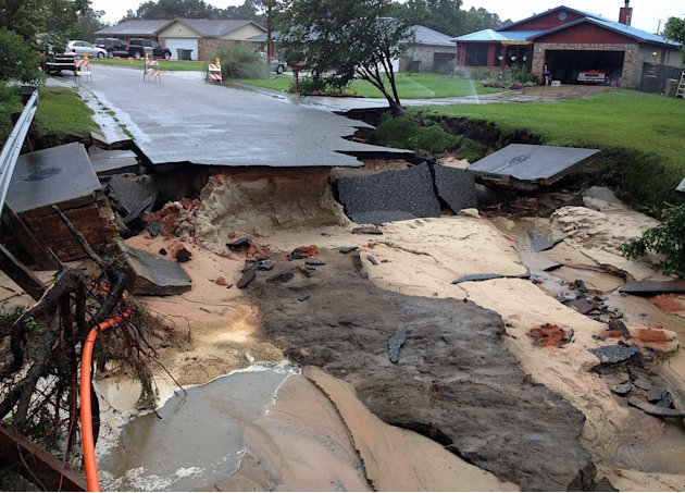 A section of Oak Valley Drive in Escambia County, Fla., is washed out on Sunday, June 10, 2012, after heavy rains fell on Saturday, in Pensacola, Fla. Floodwaters from torrential rains damaged homes a