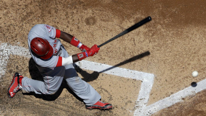 AP10ThingsToSee - Cincinnati Reds' Brandon Phillips hits an RBI ground ball during the third inning of a baseball game against the Milwaukee Brewers Wednesday, July 10, 2013, in Milwaukee. Zack Cozart scored from third. (AP Photo/Morry Gash, File)