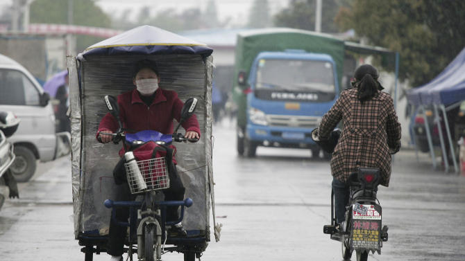 In this photo taken Wednesday, April 18, 2012, a female tricycle taxi driver makes her way through the rain in Shanghai, China. The 2 billion women living in Asia are still paid less than men for similar work and are extremely underrepresented in top leadership positions, even in wealthy countries such as Japan, according to a report issued Thursday, April 19, 2012. (AP Photo)