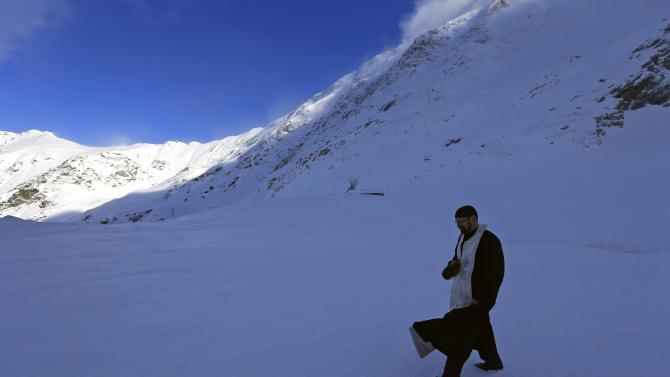 Greek Catholic priest Stefan walks to a chalet after the inauguration of a church made entirely from ice at Balea Lac resort in the Fagaras mountains