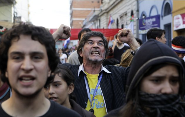 People protest against Paraguay's new President Federico Franco outside a public TV station in Asuncion, Paraguay, Sunday, June 24, 2012. Paraguay's new government battled a wave of criticism on Sunda
