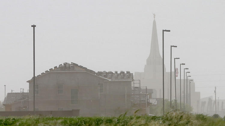 High winds create a dust haze around a new community, Monday, April 8, 2013 in Gilbert, Ariz. The National Weather Service has issued high wind and blowing dust advisories with wind gusts as high as 60 mph this afternoon and into the early evening. (AP Photo/Matt York)