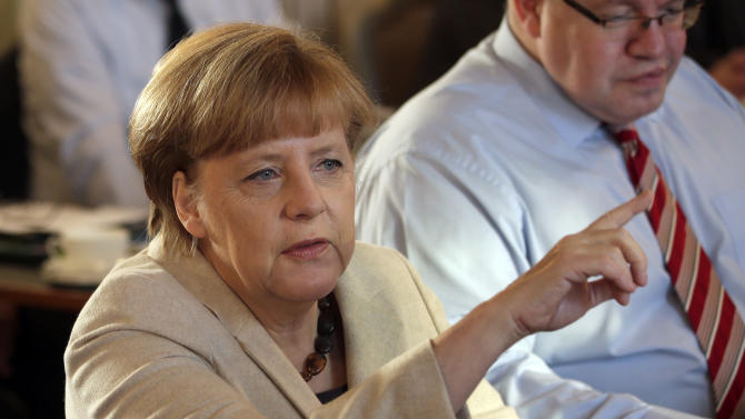 German Chancellor Angela Merkel, left, points as she and Peter Altmaier, Head of the Federal Chancellery, right, attend a cabinet meeting as part of a two day closed meeting of the German government at the Meseberg palace near Berlin, Germany, Thursday, Jan. 23, 2014. (AP Photo/Michael Sohn)
