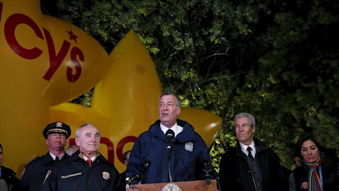 New York City Mayor Bill de Blasio speaks while New York City Police Commissioner Bratton looks on during a news conference outside the The Macy's Thanksgiving Day Parade balloon preparations in New York