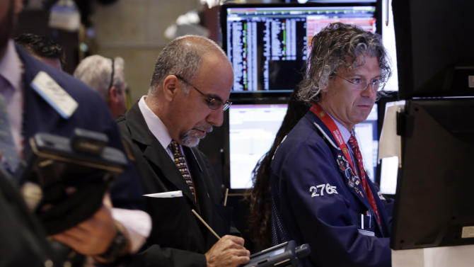 In this Monday, June 30, 2014 photo, trader John Liotti, center, and specialist Donald Civitanova, right, work on the floor of the New York Stock Exchange. World stocks were mostly higher Wednesday, July 2, 2014, on improved U.S. and Chinese economic activity. (AP Photo/Richard Drew)