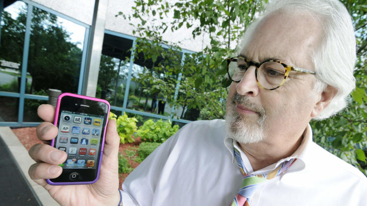 Bob Burns holds his smartphone Wednesday, June 27, 2012 in Minnetonka, Minn. Millions of smartphone users wiil soon begin receiving text messages about severe weather from a sophisticated government system that can send a blanket warning to mobile devices in the path of a dangerous storm. (AP Photo/Jim Mone)