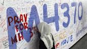 A woman writes on a banner of well wishes for the passengers of the missing Malaysia Airlines Flight MH370 at Kuala Lumpur International Airport March 14, 2014. REUTERS/Edgar Su