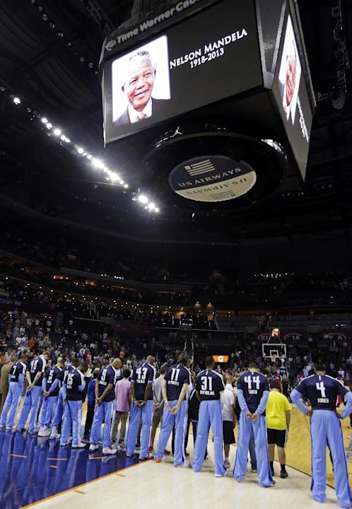 Charlotte Bobcats bow their heads in a moment of silence for former South African President Nelson Mandela, who died Thursday, before an NBA basketball game against the Philadelphia 76ers in Charlotte