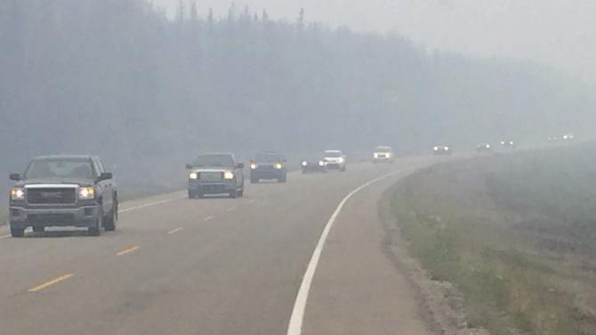 vehicles carrying evacuees from wildfires near La Ronge drive south on Highway 2 in Weyakwin