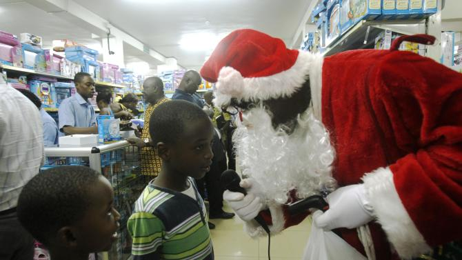 A man dressed as Santa Claus talks with children at Orca supermarket in Marcory in Abidjan