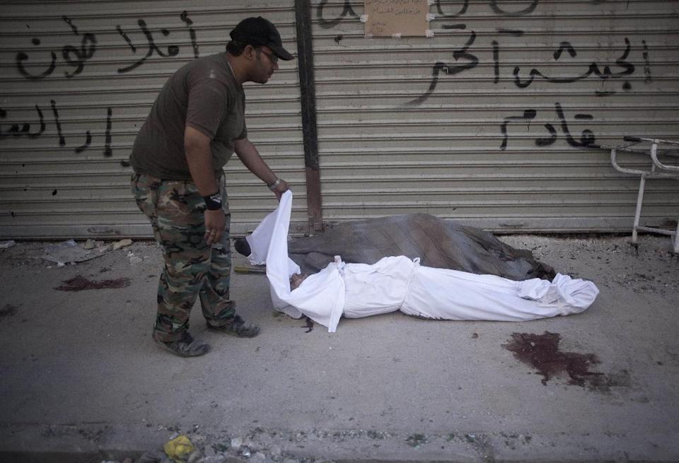 In this Thursday, Sept. 20, 2012 photo, a worker moves bodies near Dar Al Shifa hospital in Aleppo, Syria. Dozens of Syrian civilians were killed on Thursday, four children among them, in artillery shelling by government forces in the northern Syrian town of Aleppo. (AP Photo/Manu Brabo)