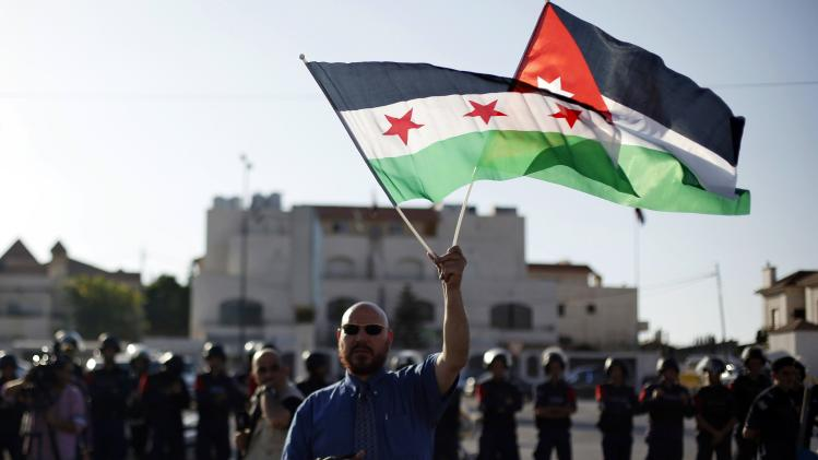 Syrian man living in Jordan holds a Syrian opposition flag and a Jordanian national flag in front of a line of Jordanian police standing guard during a demonstration near the Syrian embassy in Amman