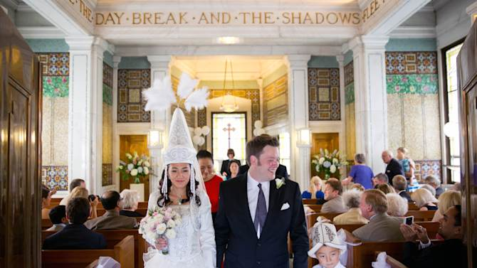 In a July 19, 2014 photo, Oliver Bonham-Carter and Janyl Jumadinova hold their wedding ceremony at the chapel at Forest Lawn Cemetery in Omaha, Neb. the bride is from Kyrgyzstan and holds a firm belief in spirits. Some of the groom's ancestors are buried in the cemetery. The couple married earlier this year in a small ceremony in Pennsylvania, but wanted to hold another ceremony so friends and family could bear witness. (AP Photo/The Omaha World-Herald/Matt Miller) MAGS OUT TV OUT US ONLY