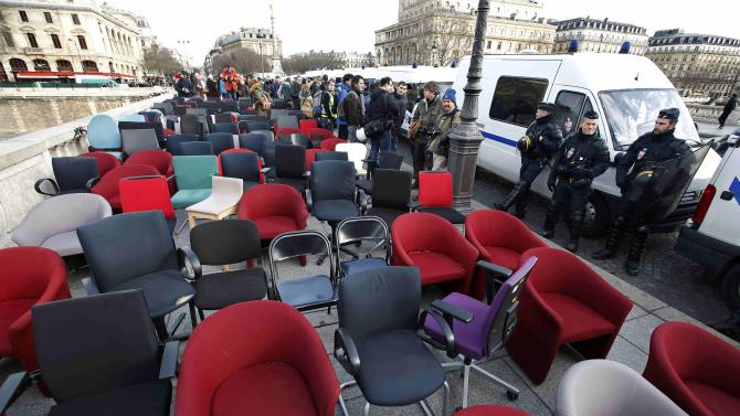 Policemen stand next to empty chairs that were stolen from bank offices in France to protest against a banking system and tax fraud, on a bridge near the courts in Paris