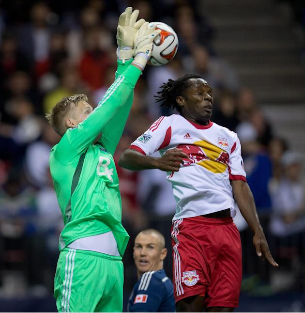 Vancouver Whitecaps' goalkeeper David Ousted, left, of Denmark, leaps to grab the ball out of the air as New York Red Bulls' Peguy Luyindula, of France, tries to get his head on it while White
