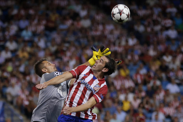 Atletico Madrid's Diego Godin from Uruguay, centre, duels for the ball with Zenit St. Petersburg's goalkeeper Yuri Lodygin during a Group G Champions League soccer match , at the Vicente Calderon stad