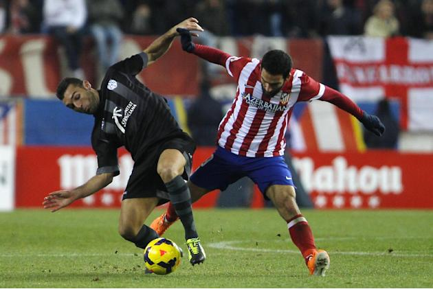 Atletico's Arda Turan from Turkey, right, competes with David Barral, left, during a Spanish La Liga soccer match between Atletico de Madrid and Levante at the Vicente Calderon stadium in Madrid,