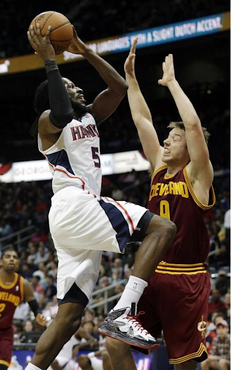 Atlanta Hawks small forward DeMarre Carroll (5) goes to the basket as Cleveland Cavaliers shooting guard Matthew Dellavedova defends in the first half of an NBA  basketball game Friday, Dec. 6, 2013,