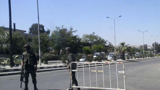 FILE -In this April 24, 2011 file photo taken with a mobile phone, through a car windscreen, showing Syrian army soldiers at a check point, in Damascus, Syria. As rebels fighting to topple President Bashar Assad edge closer toward  the Syrian capital, ushering in what many say could eventually be the final and most brutal episode of the 20-month-old civil war, Damascus residents are bracing for more hardship. (AP Photo,File)