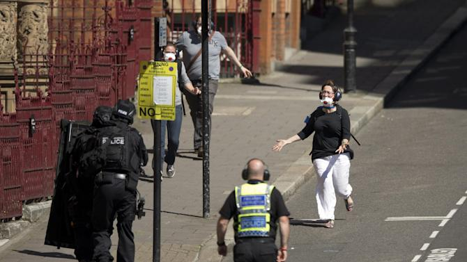 During a training exercise for London's emergency services, people run towards armed police officers as they emerge from the disused Aldwych underground train station in London, Tuesday, June 30, 2015. Hundreds of British police are taking part in a major counter-terror exercise in London, testing the abilities of emergency services to respond to a Tunisia-style attack of extremists with firearms. The exercise dubbed Operation Strong Tower has been planned for six months and is not connected to the recent attack at a north African beach resort.  (AP Photo/Matt Dunham)