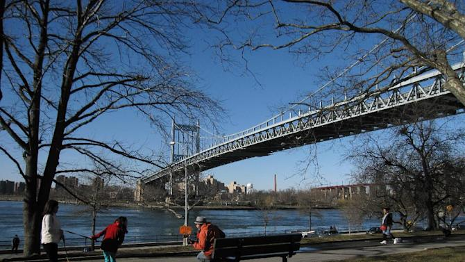 This March  9, 2013 photo shows visitors at Astoria Park in the New York City borough of Queens. It's one of several waterfront parks  in Astoria and the adjacent neighborhood of Long Island City. The area also offers museums, a variety of ethnic restaurants and moderately priced hotels with easy access to Manhattan. The photo also shows the Triborough Bridge connecting Queens with the Bronx across the water. (AP Photo/Beth J. Harpaz)