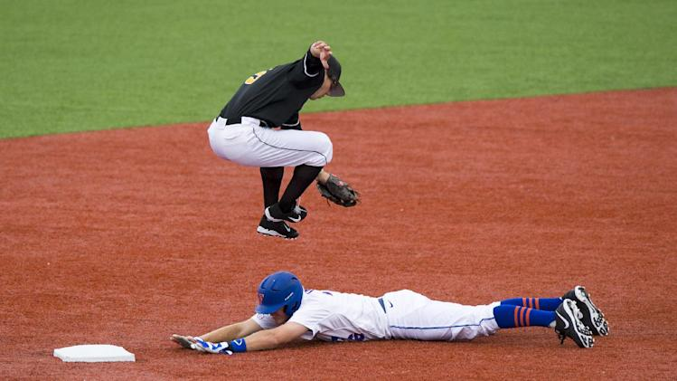 Florida's Danny Young safely slides into second base under the leap of Valparaiso second baseman Tanner Vavra during the third inning of the NCAA regional college baseball tournament Saturday, June 1, 2013, in Bloomington, Ind. (AP Photo/Doug McSchooler)