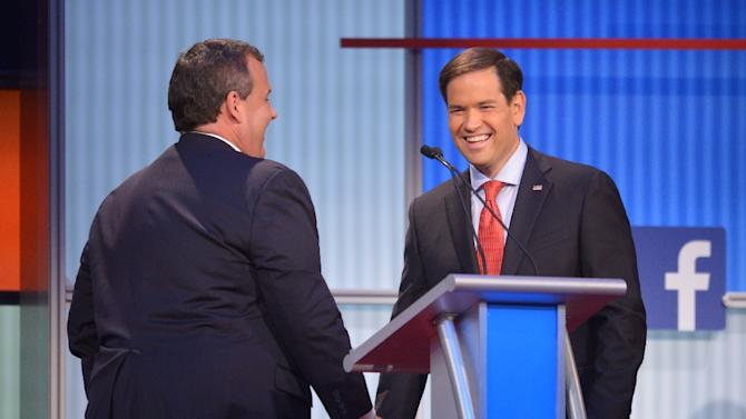 New Jersey Governor Chris Christie (L) speaks with Florida Senator Marco Rubio during a break in the Republican presidential primary debate on August 6, 2015 in Cleveland, Ohio