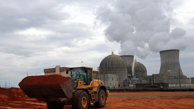 In this Tuesday, Dec. 11, 2012  photo an earth mover works on a new nuclear reactor at  the Plant Vogtle nuclear power plant in Augusta, Ga.,  One of the plant's existing reactors is shown in the background. With the cost of nuclear plants rising, a handful of state officials are showing signs of buyer's regret.  The reservations come as two of the three nuclear plants under construction have faced cost overruns just as electricity generated by natural gas has gotten cheaper. (AP Photo/John Bazemore)