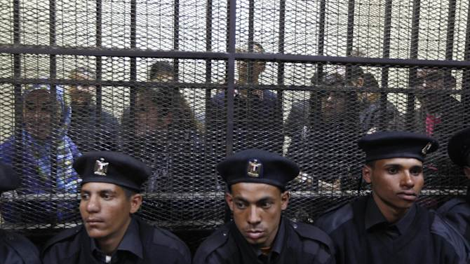 Egyptian policemen sit  in front of  Egyptian employees of several pro-democracy groups charged with using foreign funds to foment unrest during their trial in Cairo, Egypt, Sunday, Feb. 26, 2012. Egypt went forward with a trial Sunday that has plunged relations with the U.S. into the deepest crisis in decades, prosecuting 16 Americans and 27 other employees of pro-democracy groups. (AP Photo/Khalil Hamra)