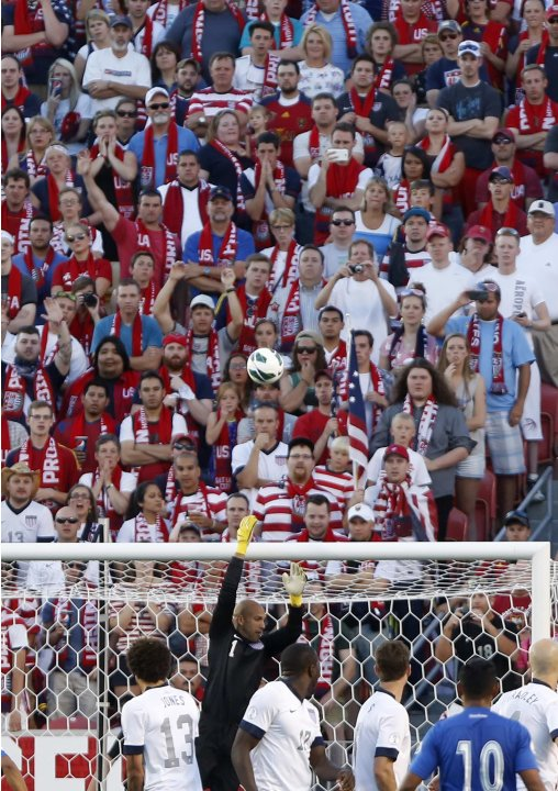 U.S. fans watch as U.S. goalkeeper Howard defends a direct kick attempt by Honduras' Martinez during their 2014 World Cup qualifying soccer match in Salt Lake City, Utah