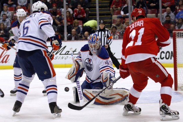 Edmonton Oilers goalie Devan Dubnyk and Oilers defensman Ryan Whitney guard their net against Detroit Red Wings center Tomas Tatar during the first period of their NHL hockey game in Detroit