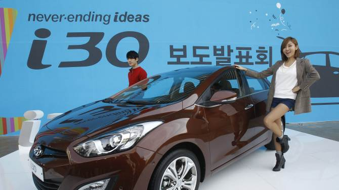 Models pose next to Hyundai Motor Co.'s i30 hatchback during an unveiling ceremony in Seoul, South Korea, Thursday, Oct. 20, 2011.The vehicle is priced from 18.4 million won to 20,1 million won. (US$16,200 - US$17,600). (AP Photo/ Ahjn Young-joon)