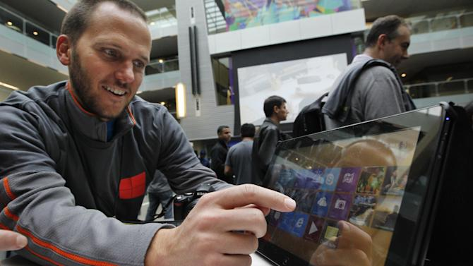 John Eversole, a marketing manager for Microsoft, uses a Samsung Series 7 Slate device with the new Windows 8 operating system during an event unveiling a new Microsoft Windows operating system Thursday, Oct. 25, 2012, at the company's headquarters in Redmond, Wash. Windows 8, attempts to bridge the gap between personal computers and fast-growing tablets with its touch-enabled interface. It is the most dramatic overhaul of the personal computer market's dominant operating system in 17 years. (AP Photo/Elaine Thompson)