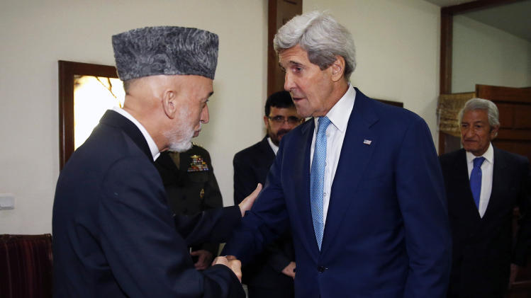 U.S. Secretary of State John Kerry, right, is greeted by Afghanistan's President Hamid Karzai as he arrives for a dinner at the presidential palace in Kabul, Afghanistan, Friday, July 11, 2014. Kerry visited Afghanistan in hopes of diffusing a crisis over the runoff presidential election to find a successor for outgoing President Karzai. (AP Photo/Jim Bourg, Pool)