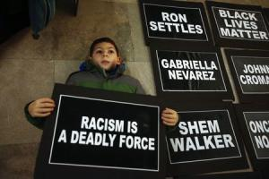 A boy joins protesters demanding justice for the death …