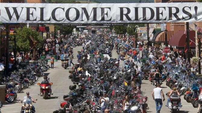FILE - This Aug. 10, 2013 file photo shows motorcycle riders on Main Street in downtown Sturgis, S.D.  Hundreds of thousands of bikers descend on the town of Sturgis, South Dakota (population: 6,600) every August for the annual Sturgis Rally gathering of motorcycle enthusiasts. This year's rally is scheduled for Aug. 5-11 and anyone can attend.  (AP Photo/Steve McEnroe, file)