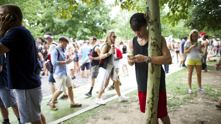 T. J. Bourne, 18, rests on a tree and texts on his mobile phone at the Made in America festival in Philadelphia