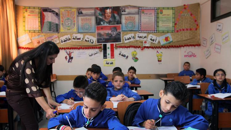 In this Wednesday, Sept. 18, 2013 photo, a Syrian teacher gives a lesson at Hassan Shuaib School in Damascus, Syria.(AP Photo)