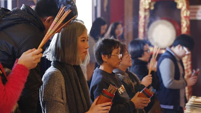 Ethnic Chinese draw bamboos sticks for divination during the celebration of the Lunar New Year at a temple in Hong Kong, Monday, Feb. 8, 2016. The celebration marks the Year of the Monkey in the Chinese calendar. (AP Photo/Kin Cheung)