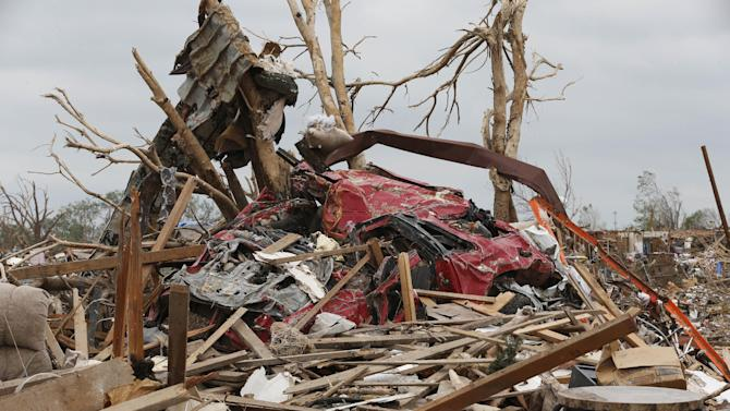 Two trees have become the resting place for twisted pieces of metal, a car and other tornado debris in Moore, Okla., Monday, May 27, 2013. (AP Photo/Sue Ogrocki)
