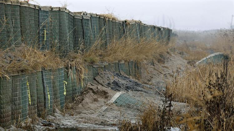 In this Dec. 8, 2012 photo, broken and battered baskets from the Richard P. Kane Wetland Mitigation Bank, a long barrier wall made of large baskets filled with sand and dirt, stand in the Meadowlands in Moonachie, N.J. The barrier was built primarily to control the movement of tidewaters in and out of the wetlands area and not for flood protection. But since the tidal surge from Superstorm Sandy washed over it and damaged more than 2,000 homes and other buildings, attention has turned to what can be done to prevent similar river flooding in future storms. Unfortunately, however, no one seems to own the problem. (AP Photo/Mel Evans)