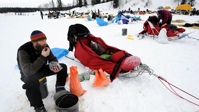 Mike Ellis eats breakfast while resting his dog team at the Finger Lake checkpoint in Alaska during the Iditarod Trail Sled Dog Race on Monday, Mar. 4, 2013. (AP Photo/The Anchorage Daily News, Bill Roth)