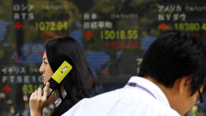 A pedestrian holding her mobile phone walks past an electronic board showing the stock market indices of various countries outside a brokerage in Tokyo