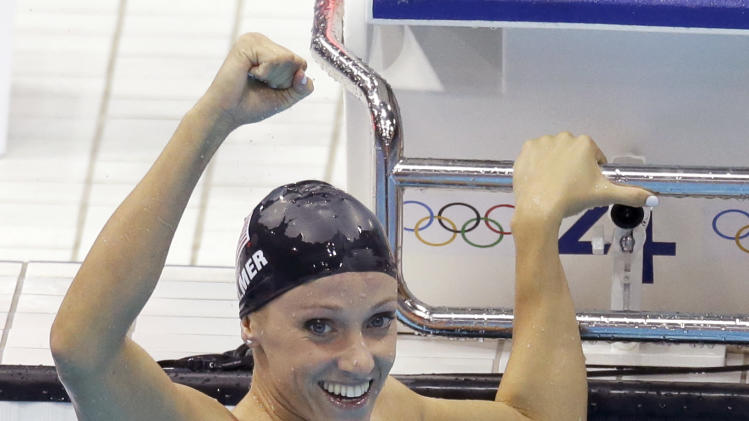 United States' Dana Vollmer celebrates her gold medal win in the women's 100-meter butterfly swimming final at the Aquatics Centre in the Olympic Park during the 2012 Summer Olympics in London, Sunday, July 29, 2012.(AP Photo/Lee Jin-man)