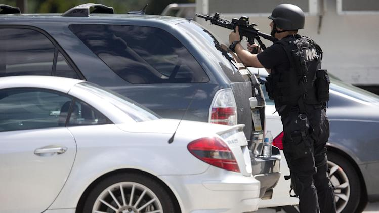 An officer points his weapon near the scene of a shooting Thursday, July 24, 2014,  at Mercy Fitzgerald Hospital in Darby, Pa. Police in suburban Philadelphia are investigating a shooting at the hospital campus and say they have reports people have been injured and a suspect is in custody. (AP Photo)
