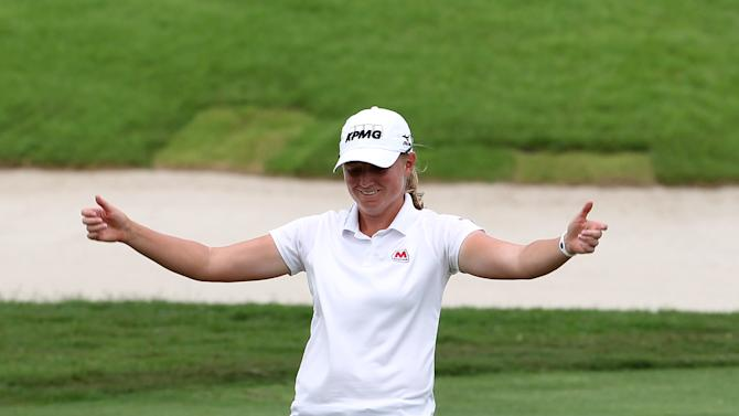 Stacy Lewis of the United States celebrates after sinking a shot on the 18th green on Sunday March 3, 2013 in Singapore to win the HSBC Women's Champions golf tournament. Lewis won the tournament on Sunday for her sixth career LPGA title, overcoming two bogeys and some shaky putting on the back nine to hold off South Korean Na Yeon Choi. (AP Photo/Wong Maye-E)