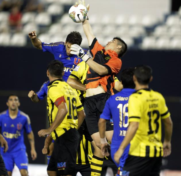 Rodrigo Mora of Chile's Universidad de Chile jumps for the ball with goalkeeper Alfredo Ariel Aguilar of Paraguay's Guarani during their Copa Libertadores soccer match in Asuncion